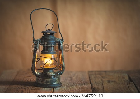 vintage kerosene oil lantern lamp burning with a soft glow light in an antique rustic country barn with aged wood floor - stock photo