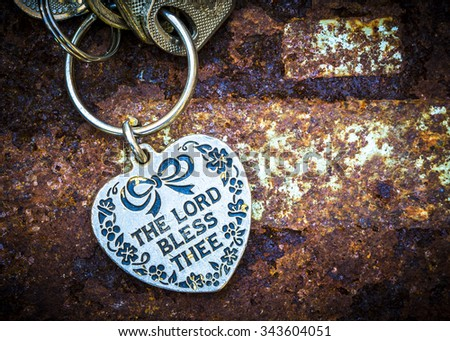 Vintage key chain with word the Lord bless thee on old rusty metal background