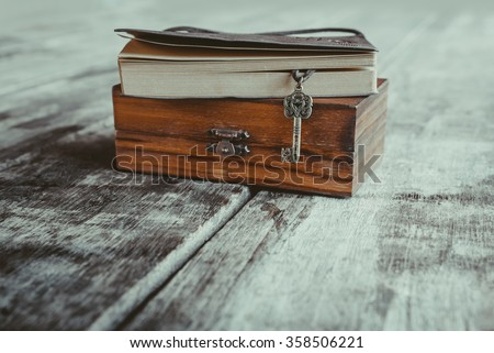vintage key heart shape and old notebook on Wood box grungy old desk - stock photo