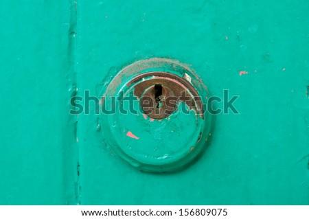 Vintage key hold on green door - stock photo