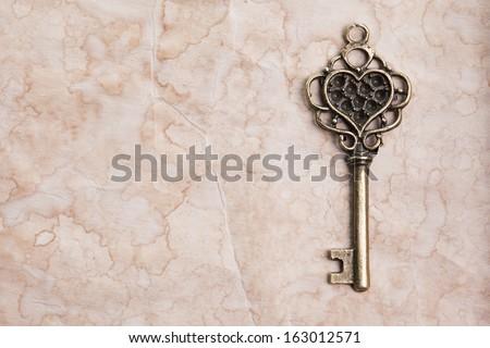 Vintage key on paper background - stock photo