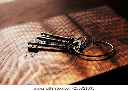 Vintage keys on an grungy old desk with window light shadow. Shallow depth of focus. - stock photo
