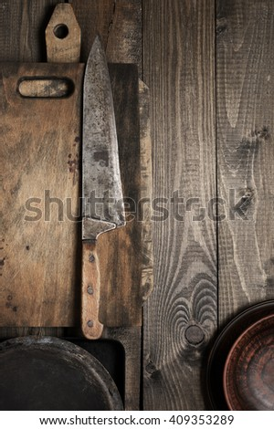 Vintage kitchen cooking utensils on rough wooden background: cutting boards, knife and crockery. Top view point.