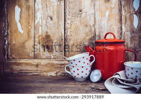 Vintage kitchen decor, red enamel coffee pot and cups with polka dots on an old wooden board background with copy space. Rustic home decor. - stock photo