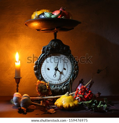 Vintage kitchen scales with a candle and vegetables - stock photo