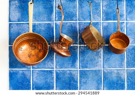 Vintage kitchen tools. Copper kitchenware set. Pots, coffee maker, colander hanging on. Blue tile wall background. - stock photo