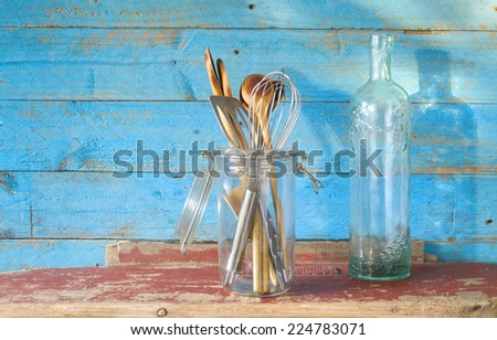 vintage kitchen utensils, wooden spoons and an old ornamented bottle - stock photo