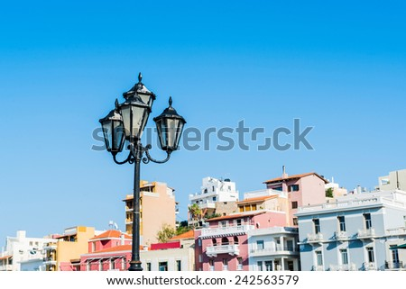 vintage lamp in the picturesque town of Agios Nikolaos with colorful houses (blue sky background) - stock photo