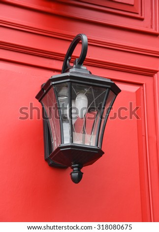 Vintage lamp post on a red wall - stock photo