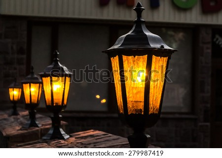 Vintage lampposts at dusk in perspective - stock photo