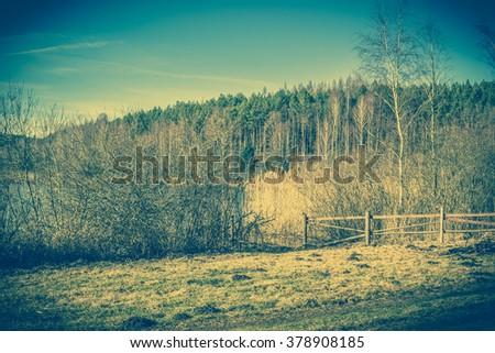 Vintage landscape of farm near lake. - stock photo