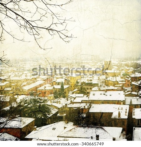 Vintage landscape of snow-covered roofs with bare branches - stock photo
