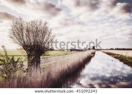 Vintage landscape with windmill and clouds reflection in water, traditional Holland view - stock photo