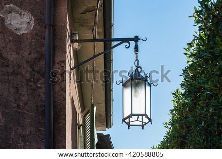 Vintage lantern hanging on old building's wall against blue sky / Vintage lantern fixed to building's wall with blue sky / Italian architecture in Tuscany with street light and clear sky