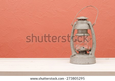 Vintage lantern on white  table with pink / coral background wall. Great interior accent and has plenty of room for advertisement.  - stock photo