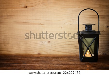 Vintage Lantern with burning Candle on wooden table. filtered image
