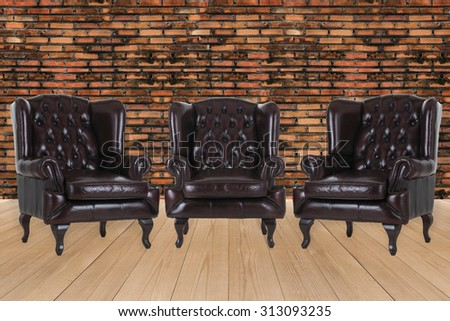 Vintage leather armchair on brick wall texture background
