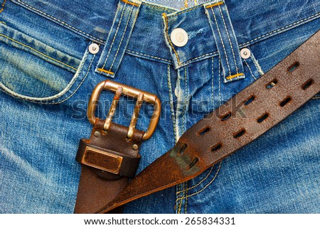 Vintage leather belt with metal buckle on old blue jeans - stock photo