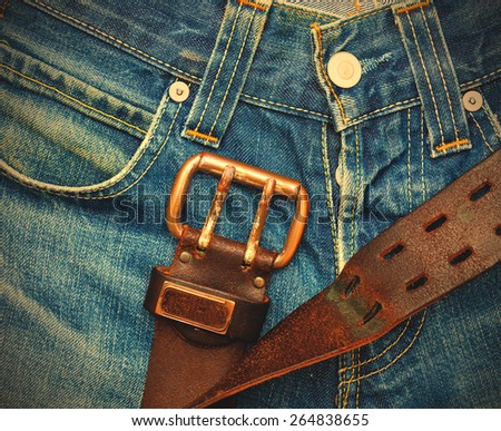 Vintage leather belt with metal buckle on old blue jeans. instagram image retro style - stock photo