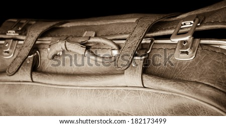 Vintage leather briefcase with straps and brass buckles on black background. Travel concept. Sepia. Selective focus on the right side of the image.