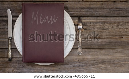 Vintage leather restaurant or cafe food menu with silverware or cutlery including a fork and a knife on top of a stack of white classic plates on a rustic wood table background