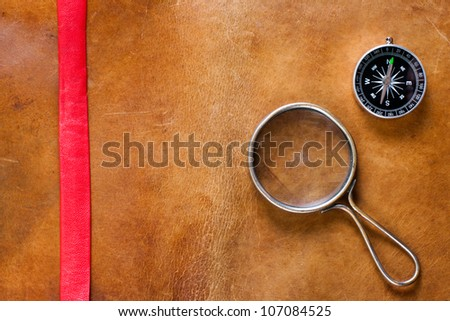Vintage leather with magnifying glass and compass - stock photo