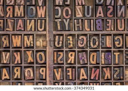 vintage letterpress wood type printing blocks  in a grunge typesetter drawer - stock photo