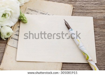 Vintage letters and persian buttercup flowers (ranunculus) on wooden background, copy space - stock photo