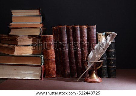 Vintage library. Feather against set of old books in a row