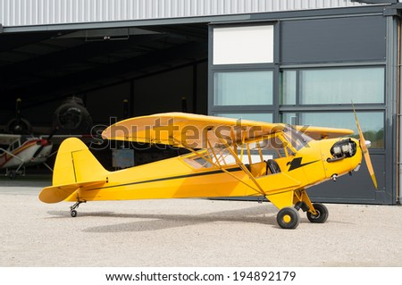 Vintage little yellow plane in front of a hangar - stock photo