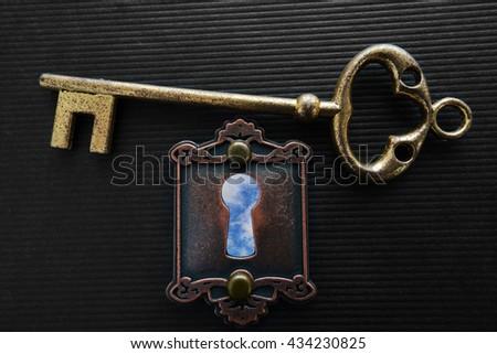 Vintage lock and key with blue sky keyhole                                - stock photo