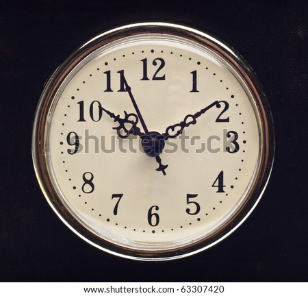 Vintage Look Clock on Black Leather Hands at 10 and 2. - stock photo