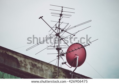 Vintage look filter, Old antenna and red dish satellite receiver with blue sky background. Silhouetted image (antenna, television, silhouetted) - stock photo