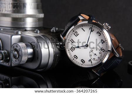 Vintage look marine watches with white dial, and arabic numbers, blued hands, onion crown on blue alligator leather strap with retro soviet 35mm photo rangefinder camera on black background - stock photo
