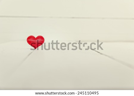 Vintage look of a single heart shape on white wooden background. Valentines Day background. Shallow depth of field - stock photo