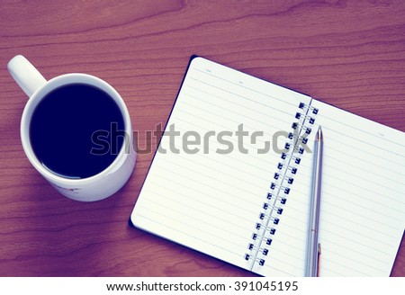 Vintage look of top view on opened notebook, pen and cup of coffee on wooden office desk. - stock photo