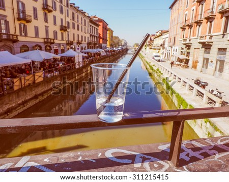 Vintage looking A glass of alcoholic cocktail drink on a bridge at Naviglio Grande canal waterway which is the main nightlife place in Milan Italy - focus on glass, with blurred background - stock photo