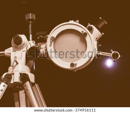 Vintage looking Astronomical telescope over dark sky with the moon - selective focus on telescope