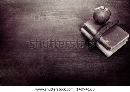 Vintage Looking Desk with leather belt wrapped around books and apple on top of them - stock photo