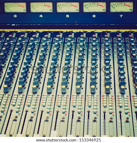 Vintage looking Detail of a soundboard mixer electronic device - stock photo