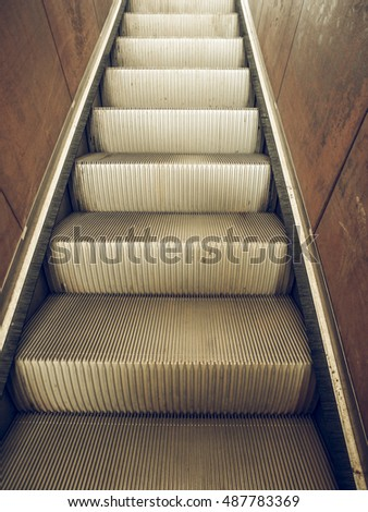 Vintage looking Escalator stairs to an underground station or supermarket