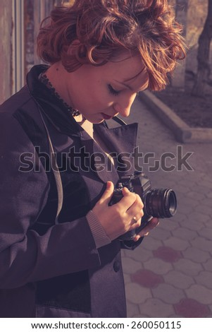 Vintage looking instagram style toned colors image of redhead women with camera in her hands - stock photo