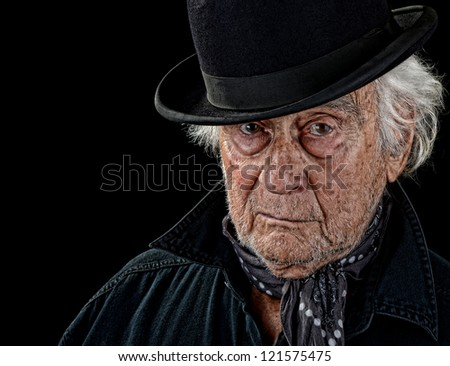 Vintage looking old man with a black coat, gray scarf and black bowler hat staring straight at the camera isolated on black - stock photo