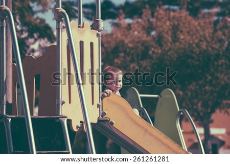 Vintage looking photo of a child boy on a slide at children playground. - stock photo