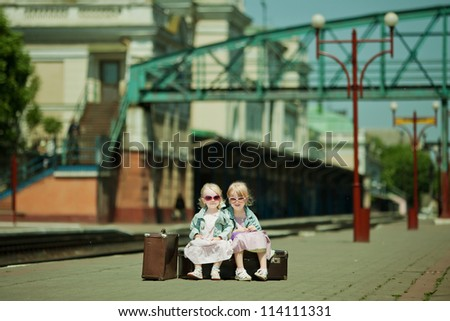 Vintage looking picture of small girls with luggage at the railway station - stock photo