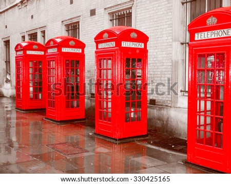 Vintage looking Red telephone box in London over desaturated black and white background - stock photo