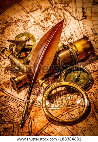 Vintage magnifying glass, compass, goose quill pen and spyglass lying on an old map. - stock photo