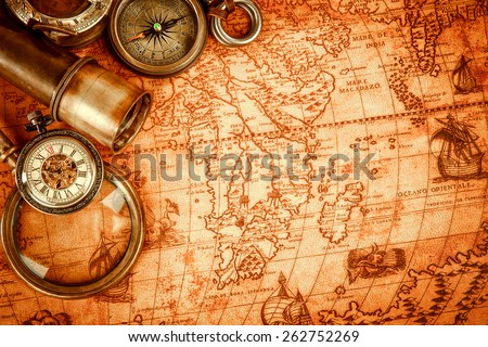 Vintage magnifying glass, compass, telescope and a pocket watch lying on an old map in 1565. - stock photo