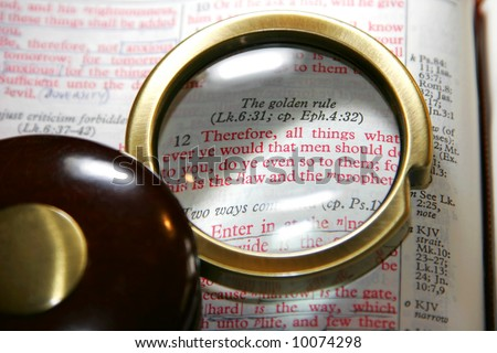 Vintage magnifying glass on a Holy Bible, highlighting the Golden Rule passage in Matthew Chapter 7 - King James Version (shallow focus). - stock photo