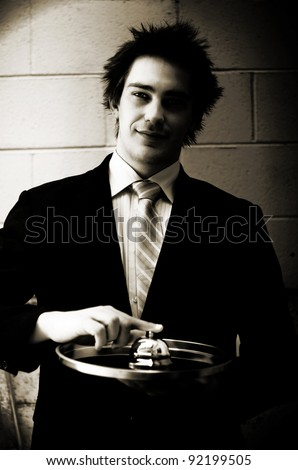 Vintage Male Concierge  Or Business Man Pressing The Button On A Hotel Desk Service Bell In A Depiction Of Good Old Fashioned Service With A Smile - stock photo